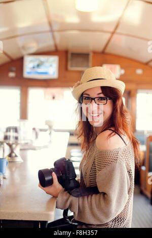 Mujer caucásica sosteniendo la cámara en restaurante.