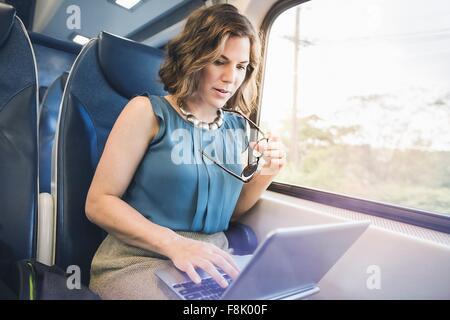 Mitad mujer adulta en el tren, utilizando el portátil