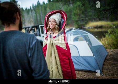 Joven mujer vistiendo knit hat envuelto en saco de dormir, Lake Tahoe, Nevada, EE.UU.