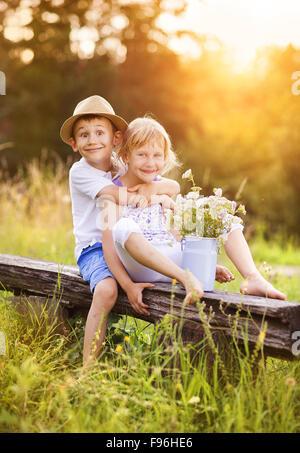 Lindo chico y chica en el amor. Ellos sentados en un banco al atardecer.