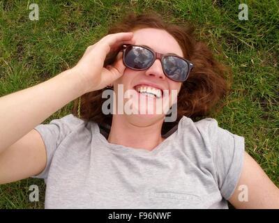 Mujer sonriente tumbado sobre el césped