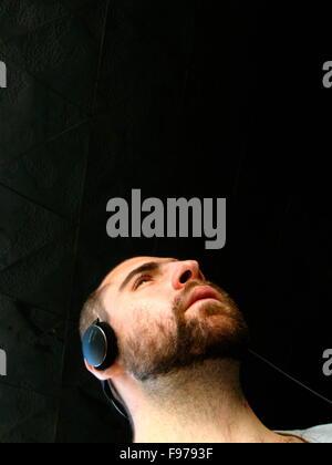 Primer plano de un joven serio usando audífonos