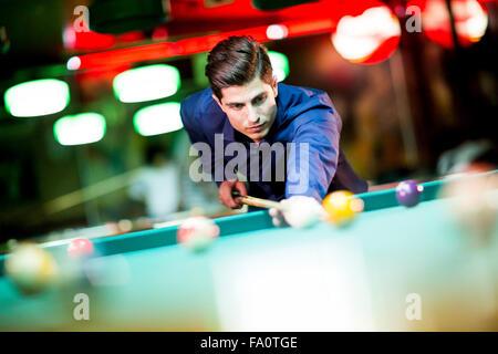 Joven jugando al billar en el bar