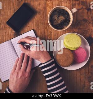 Mujer escribiendo en el portátil durante el desayuno, vista superior de manos femeninas con lápiz, taza de café, teléfono móvil y macaron cookie