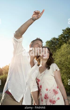 Hombre maduro mostrando algo a su esposa en lakeside, Baviera, Alemania