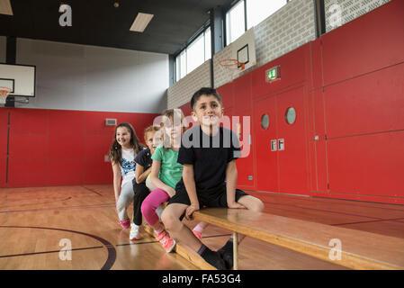Los niños descansando en un banco antes de ejercicios en el gimnasio de la escuela de Baviera, Múnich, Alemania