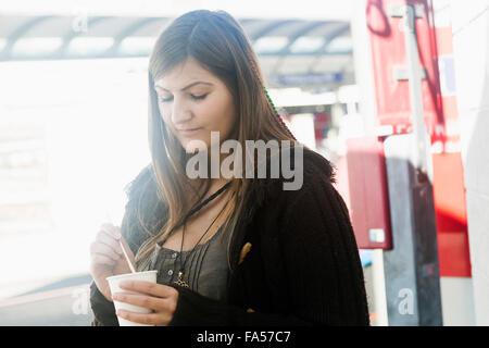 Mujer joven bebiendo café en la ciudad de Friburgo de Brisgovia, Baden-Wurtemberg, Alemania