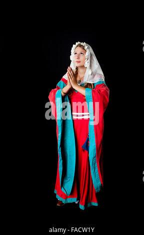 Foto de estudio de hermosa niña vestida con traje medieval vestido y pañuelo orando sobre fondo negro Foto de stock