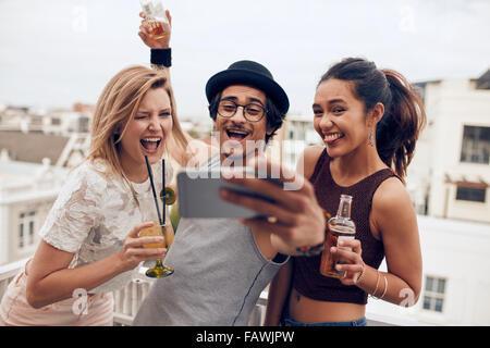 Un pequeño grupo de amigos tomando selfie en un teléfono móvil. El hombre y la mujer joven con bebidas haciendo cara divertida mientras toma un auto po