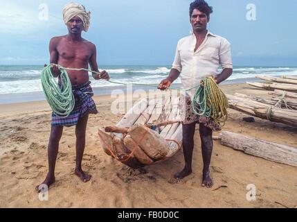 Dos pescadores indios permanecer juntos por su barco hecho crudo de registros y sujetar la cuerda en sus manos hacia adelante en la playa