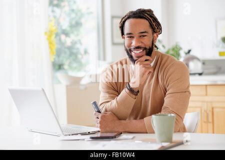Retrato del joven sonriente con laptop en la mesa