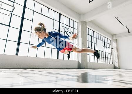 Ángulo de visión baja de la mujer joven en el gimnasio haciendo subir el aire.