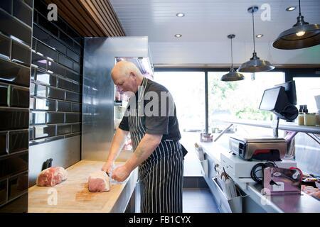 Carnicero maduro preparar carne en carnicerías shop Foto de stock