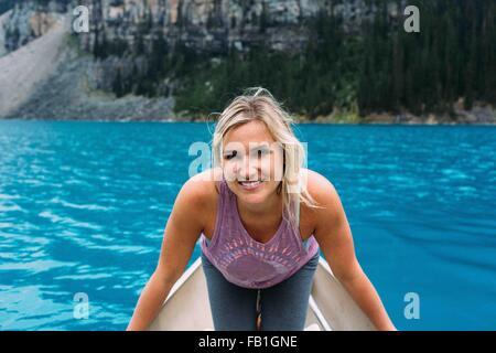 Retrato de mujer adulta media en canoa en el lago Moraine, mirando a la cámara sonriendo, Parque Nacional de Banff, Alberta, Canadá