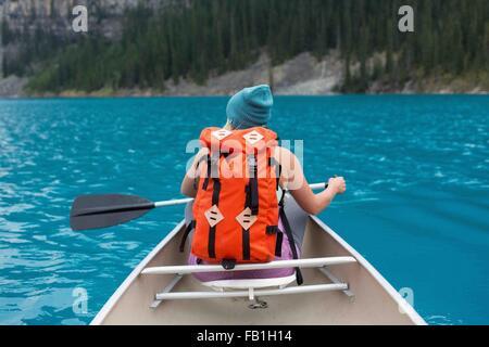 Vista trasera de mediados de mujer adulta con color naranja mochila remando en canoa, el lago Moraine, el Parque Nacional de Banff, Alberta, Canadá