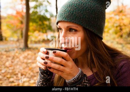 Mujer joven bebiendo café en otoño bosque