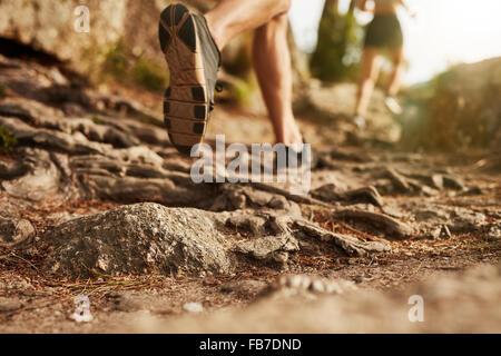 Cross Country en ejecución. Primer plano del macho pies corren a través de terreno rocoso. Se centran en los zapatos.