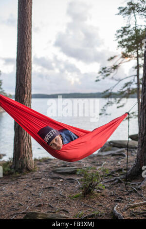 Suecia, Vastergotland, Lerum, Boy (12-13) acostado en la hamaca en el lago al atardecer Harsjon