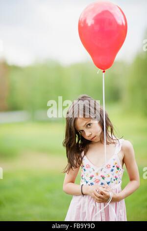 Suecia, Vastmanland, Bergslagen, linda chica (6-7) que sujetan el globo rojo