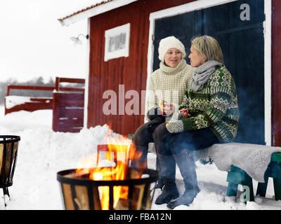 Suecia, hablando con la madre adolescente (14-15) en un banco en invierno