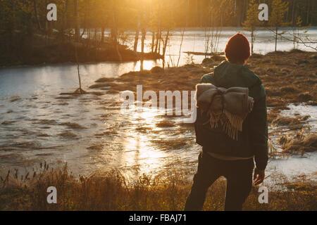 Finlandia, Esbo, Kvarntrask, joven parado en la orilla de lago pantanoso