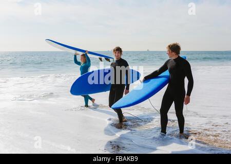 Portugal, Lisboa, tres personas llevar tablas de surf en la playa