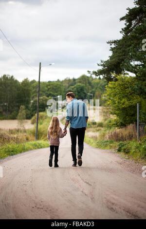 Finlandia, Uusimaa, Raasepori, Karjaa, Padre caminando con su hija (6-7) a lo largo de country road