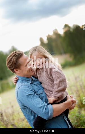 Finlandia, Uusimaa, Raasepori, Karjaa, Padre sostiene en brazos a su hija (6-7)
