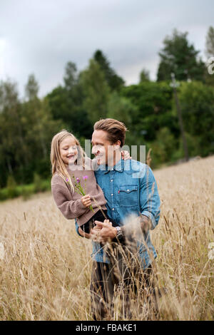 Finlandia, Uusimaa, Raasepori, Karjaa, Padre sosteniendo a su hija (6-7) en el campo de cultivo