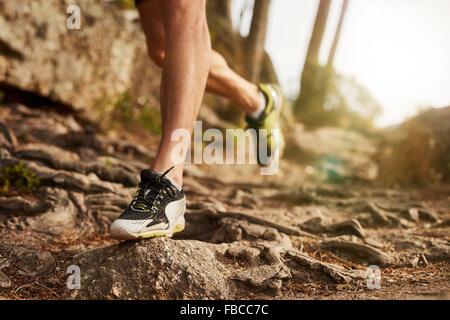 Close-up de trail running shoe sobre desafiantes terrenos rocosos. Macho de las piernas del corredor trabajando en terrenos extremos al aire libre.