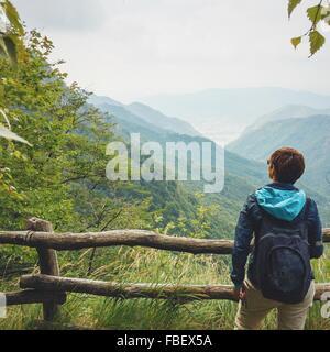 Vista trasera del hombre con mochila estando en contra de las montañas