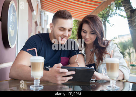 Retrato de la feliz pareja joven sonriente sentado en la cafetería de la calle compartiendo auriculares, celebración de tabletas y mirar la pantalla, dos g Foto de stock