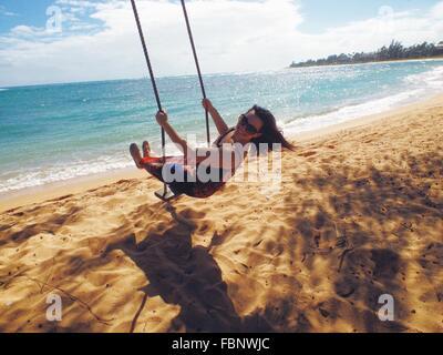 Mujer en la playa Swing Foto de stock