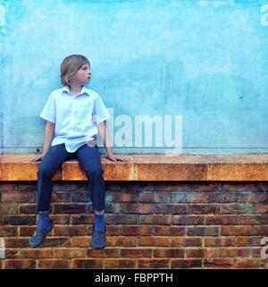 Adolescente vistiendo la camisa azul y jeans sentados en el muro