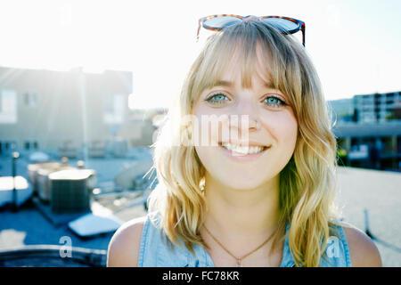 Mujer caucásica sonriendo en la azotea urbana