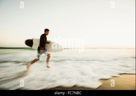 Hombre caucásico llevar tablas de surf en la playa