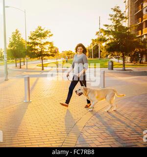 Mujer caucásica caminar perro en la acera