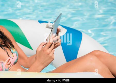Mujer caucásica mediante tableta digital en piscina