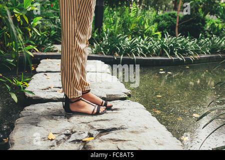 Mujer caucásica de pie sobre la piedra en el estanque Foto de stock