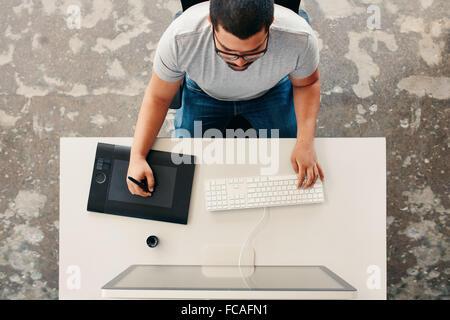 Vista superior de un hombre diseñador gráfico utilizando digital tableta gráfica y escritorio en la oficina. Editor de dibujo sentado en su escritorio