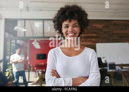Sonriente joven mujer de pie con los brazos cruzados y mirando a la cámara. Ella está de pie en una oficina moderna con sus colegas