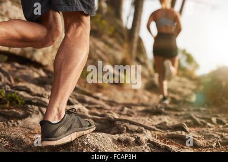 Primer plano del macho pies corren a través de terreno rocoso. Cross Country funcionando con foco en las piernas del corredor.