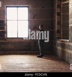 El perfil lateral de un hombre mirando hacia afuera de la ventana