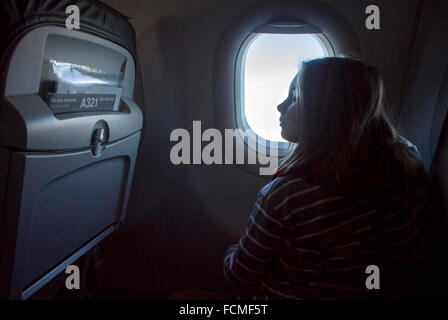 Niña mirando por la ventana del avión mientras avión está volando.