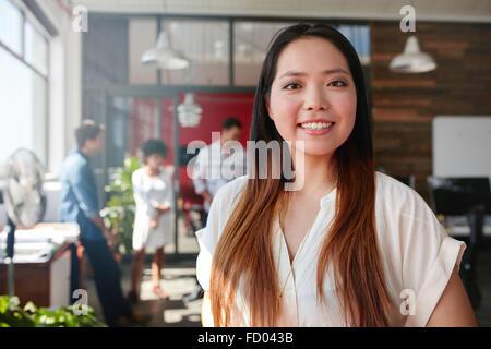 Sonriente joven empresaria mirando a la cámara y sus colegas están de pie en el fondo. Joven asiático femenino pro creativa