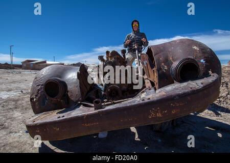 Hombre joven sentado en el viejo coche oxidado, cementerio de los trenes, municipio de Uyuni, departamento de Potosí, Foto de stock