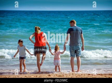 Una pareja remando con sus hijos en Boscombe Playa, Bournemouth UK