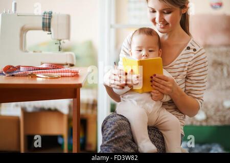 La madre y el bebé leyendo un libro juntos en casa.