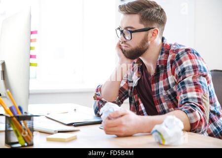 Joven apuesto hombre barbado en camisa a cuadros pensando y abollado el papel en su lugar de trabajo