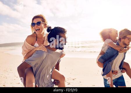Los hombres jóvenes felices dando piggyback ride a la mujer en la playa. Diverso grupo de jóvenes divirtiéndose en la playa y aprovechar.